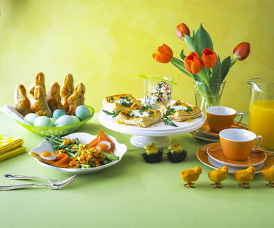 Food arranged on table against yellow wall during Easter - PPXF00241