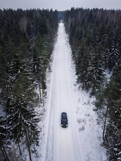 Aerial view of a car driving on a snowy road surrounded by the forest in Estonia - AAEF02486