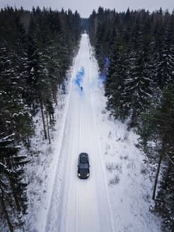 Aerial view of a man lighting a blue smoke grenade on a snowy road in the forest in Estonia - AAEF02489