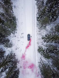 Aerial view of a man lighting a pink smoke grenade on a snowy road in the forest in Estonia - AAEF02492