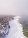 Aerial view of the snowy misty coast of Muraste in Estonia - AAEF02495
