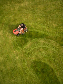 Aerial view of a man mowing the lawn creating shapes. - AAEF02690