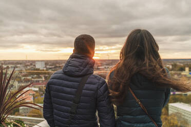 Couple watching the sunset over thecity from a view terrace, Tallinn, Estonia - TAMF02138