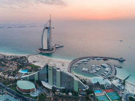 Aerial view of the luxurious Burj Al Arab Hotel and harbour at sunset on Dubai coast, UAE - AAEF02713