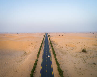 Aerial view of a straight road in Qdra desert in Dubai, U.A.E. - AAEF02719