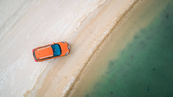 Aerial view of a car parked close by Al Qudra lakes in the middle of Saih Al Salam Desert in Dubai, UAE. - AAEF02770