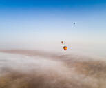 Aerial view of a group of hot-air-balloon flying in the clouds of the Murqquab desert in Dubai, UAE - AAEF02884