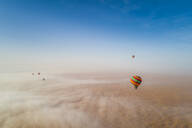 Aerial view of hot-air-balloon flying in the clouds of the Murqquab desert in Dubai, UAE - AAEF02890