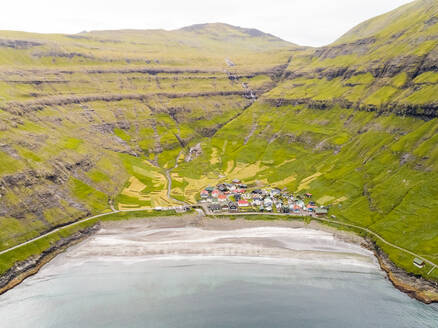 Aerial view of small village surrounding by mountain elevations, Faroe island - AAEF02977
