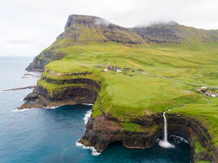 Aerial view faraway of Múlafossur waterfall near a small village, Faroe island. - AAEF02983
