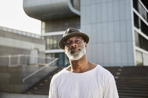 Portrait of smiling mature man with grey beard wearing hat in summer - FMKF05882