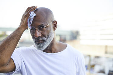 Portrait of mature man wiping his bald on hot summer day - FMKF05888