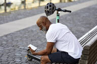 Mature man with E-Scooter sitting on bench in summer using mini tablet, Cologne, Germany - FMKF05894