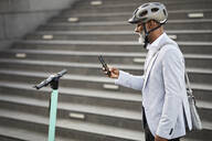 Mature businessman with E-Scooter wearing cycling helmet looking at cell phone - FMKF05897