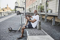 Portrait of mature man with E-Scooter relaxing on bench in summer using cell phone, Cologne, Germany - FMKF05903