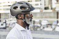 Profile of mature businessman with grey beard wearing cycling helmet and glasses - FMKF05906