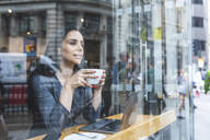 Business woman having a coffee and looking out of the window - WPEF01797
