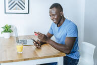Young man with credit card and smartphone at home - KIJF02586