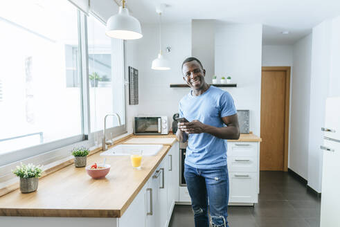 Portrait of happy young man using cell phone in kitchen at home - KIJF02595