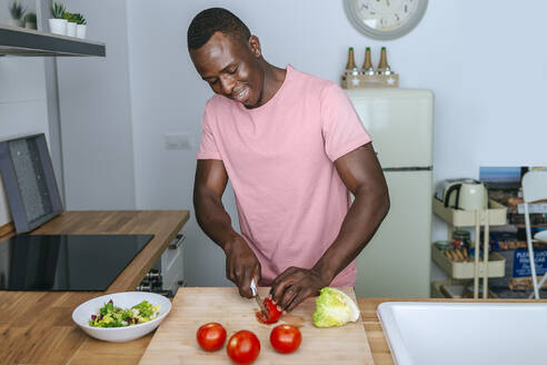 Young man in kitchen cutting tomato for a salad - KIJF02598