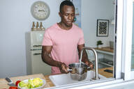 Young man pouring water into pot in kitchen - KIJF02604
