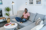 Young man with headphones and smartphone on couch at home - KIJF02610