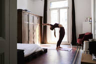 Young brunette woman practising yoga in student dorm - IGGF01272