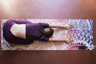 Young brunette woman practising yoga in student dorm, child position from above - IGGF01290