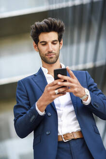 Businessman using cell phone outside an office building - JSMF01220