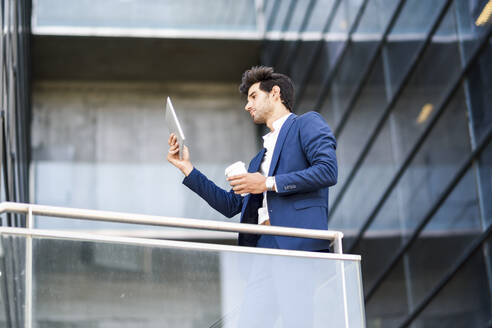 Businessman using tablet on balcony of an office building - JSMF01229