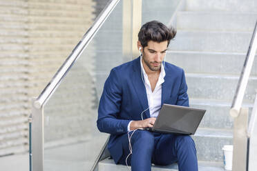 Businessman wearing earphones using laptop outdoors in the city - JSMF01235