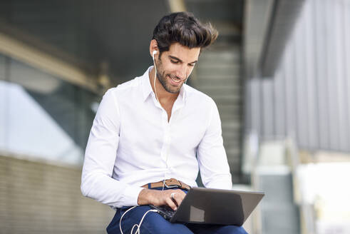Smiling businessman wearing earphones using laptop outdoors in the city - JSMF01238