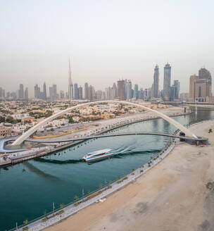 Aerial view of a yacht under the Tolerance pedestrian Bridge with Dubai skyscrapers in background, U.A.E. - AAEF03193