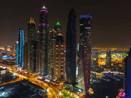 Aerial view of illuminated skyscrapers at night in Dubai, United Arab Emirates. - AAEF03325