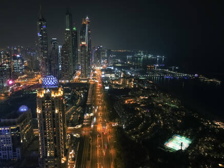 Aerial view of illuminated skyscrapers at night in Dubai, United Arab Emirates. - AAEF03328