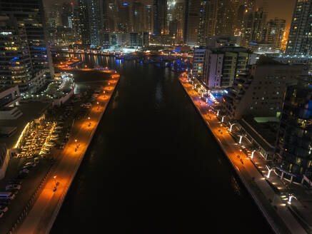 Aerial view of Dubai canal and illuminated buildings at night, United Arab Emirates. - AAEF03343