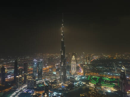 Aerial view of illuminated Burj Khalifa Tower at night in Dubai, United Arab Emirates. - AAEF03346