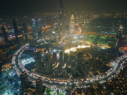 Aerial view of illuminated skyscrapers and Burj Khalifa Tower at night in Dubai, United Arab Emirates. - AAEF03349