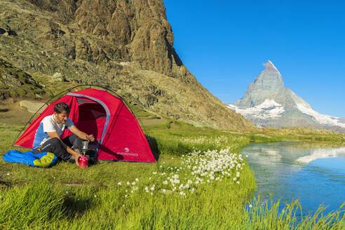 Hiker at lake Riffelsee makes coffee outside tent facing the Matterhorn, Zermatt, canton of Valais, Swiss Alps, Switzerland, Europe - RHPLF01651