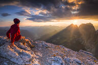Hiker looks at sunset from Piz Pordoi, Fassa Valley, Trentino, Dolomites, Italy, Europe - RHPLF01705