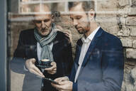 Senior and mid-adult businessman sharing a tablet - GUSF02392