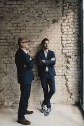 Senior and mid-adult businessman standing at brick wall - GUSF02395