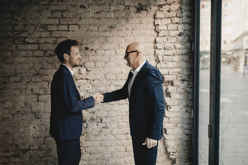 Senior and mid-adult businessman shaking hands - GUSF02401