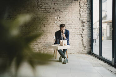 Businessman sitting at brick wall looking at architectural model - GUSF02404