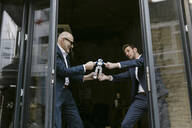 Senior and mid-adult businessman fighting for robot - GUSF02419