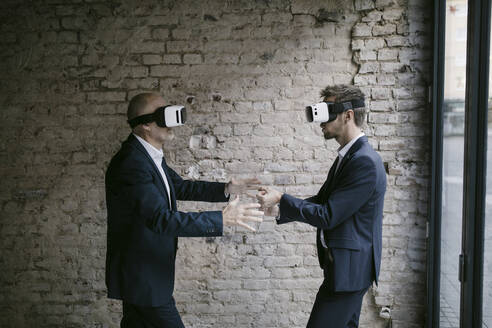 Senior and mid-adult businessman wearing VR glasses - GUSF02422