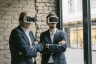 Senior and mid-adult businessman wearing VR glasses - GUSF02443