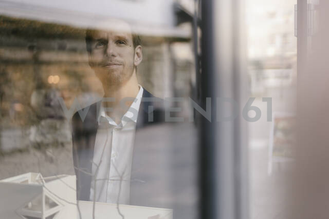 Portrait of businessman with architectural model looking out of window - GUSF02458 - Gustafsson/Westend61
