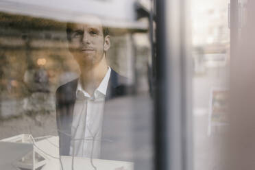 Portrait of businessman with architectural model looking out of window - GUSF02458