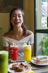 Laughing young woman drinking a smoothie in a cafe - MGIF00675